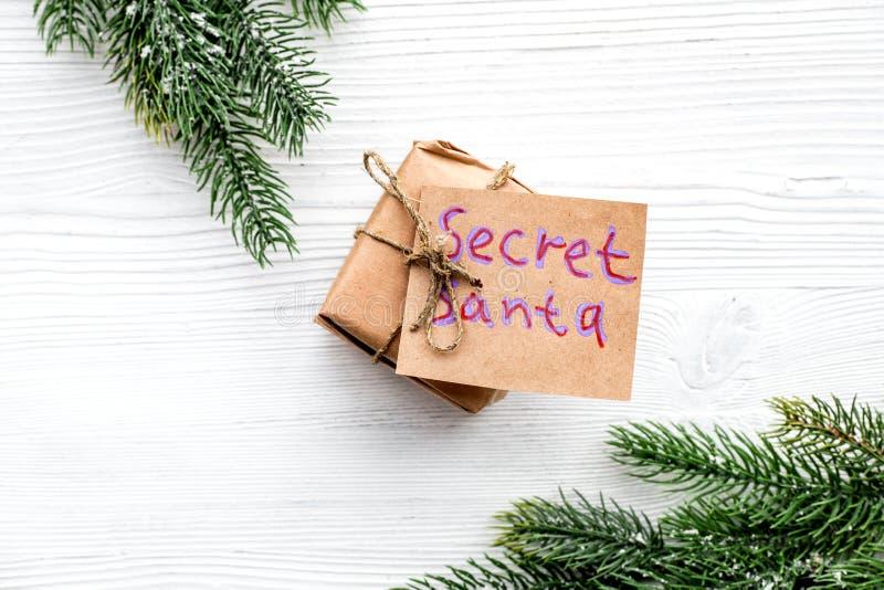 Weihnachtsspiel Wichteln Geschenkbox nahe Fichtenzweig auf weißem hölzernem copyspace Draufsicht des Hintergrundes lizenzfreie stockbilder