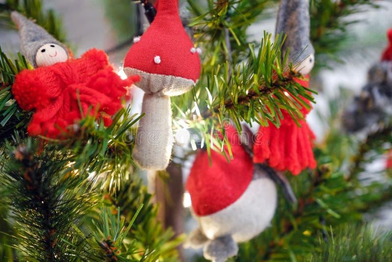Weihnachtsspielwaren, die an den Niederlassungen, unter den Weihnachtsbaumgeschenken für hängen Girlanden brennen lizenzfreie stockfotos