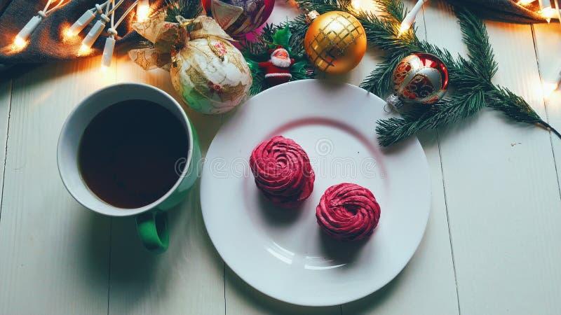 Weihnachtsspielwaren, eine Schale heißer Tee, Eibische und Weihnachtsbaumgirlande auf einer weißen Tabelle lizenzfreie stockfotos
