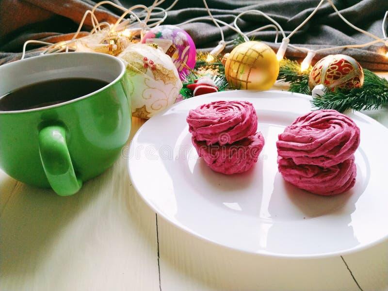 Weihnachtsspielwaren, eine Schale heißer Tee, Eibische und Weihnachtsbaumgirlande auf einer weißen Tabelle stockbilder