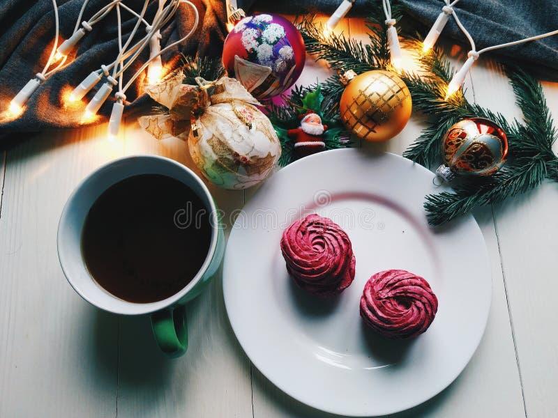 Weihnachtsspielwaren, eine Schale heißer Tee, Eibische und Weihnachtsbaumgirlande auf einer weißen Tabelle lizenzfreie stockfotografie