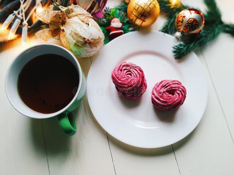 Weihnachtsspielwaren, eine Schale heißer Tee, Eibische und Weihnachtsbaumgirlande auf einer weißen Tabelle lizenzfreie stockbilder