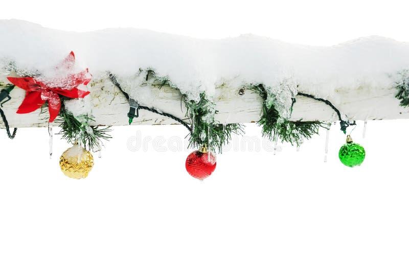 Weihnachtsspielwaren und -girlanden mit Kiefernniederlassungen auf dem alten Bretterzaun bedeckt mit Eis und Eiszapfen auf einem  lizenzfreie stockfotografie