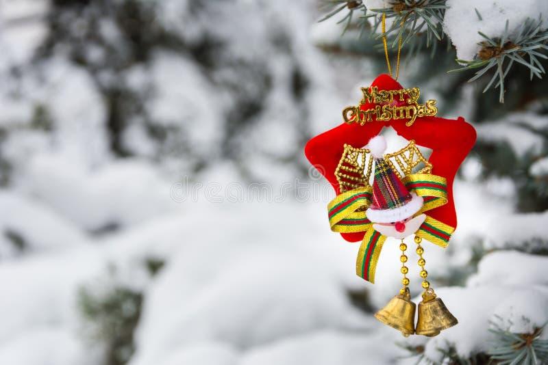 Weihnachtsspielzeug auf einem schneebedeckten Baumast stockbilder