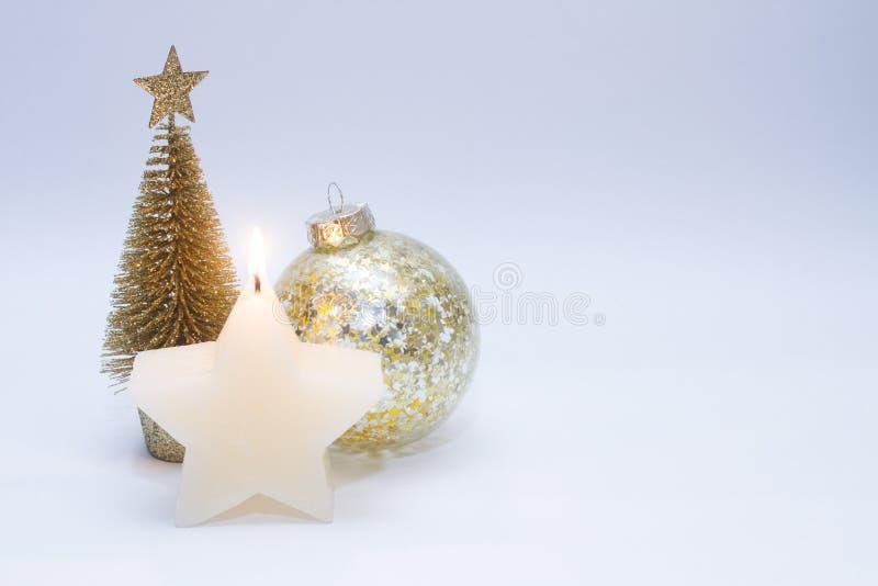 Weihnachtsspielzeug, Baum, Ball der goldenen Farbe und eine brennende Kerze Neues Jahr auf einem grauen Hintergrund lizenzfreie stockbilder