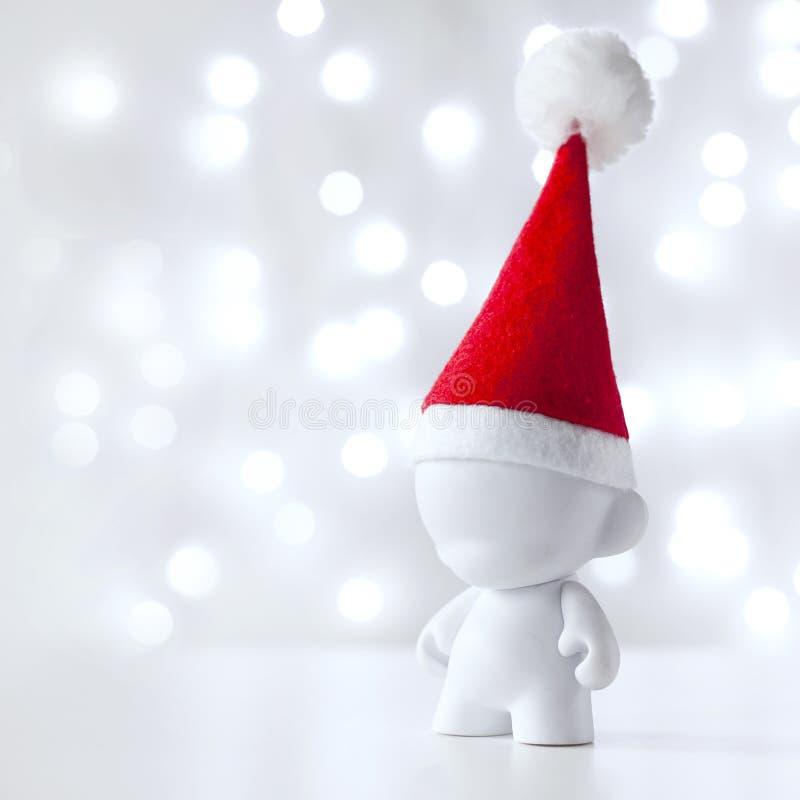 Weihnachtsspielzeug in Red Hat Santa Claus, Symbol-neues Jahr, Defocused Licht-Weiß-Hintergrund lizenzfreies stockbild