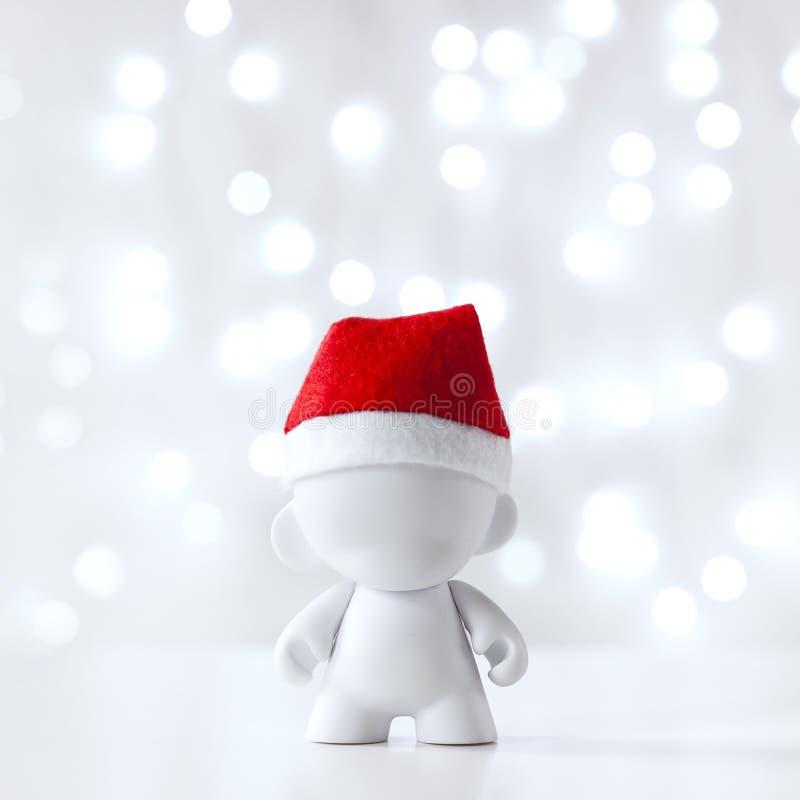 Weihnachtsspielzeug in Red Hat Santa Claus, Symbol-neues Jahr, Defocused Licht-Weiß-Hintergrund lizenzfreie stockfotografie