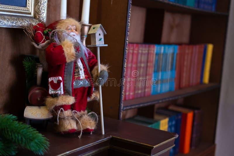 Weihnachtsspielzeug Santa Claus ist- im Regal in der Bibliothek Hintergrundbücherregal bokeh Neues Jahr ` s Innenraum lizenzfreie stockfotos