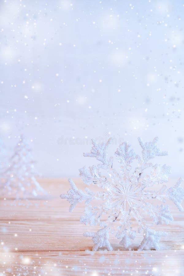 Weihnachtsspielzeugschneeflocke steht auf Holztisch auf hellblauem Hintergrund mit Schnee lizenzfreie stockbilder