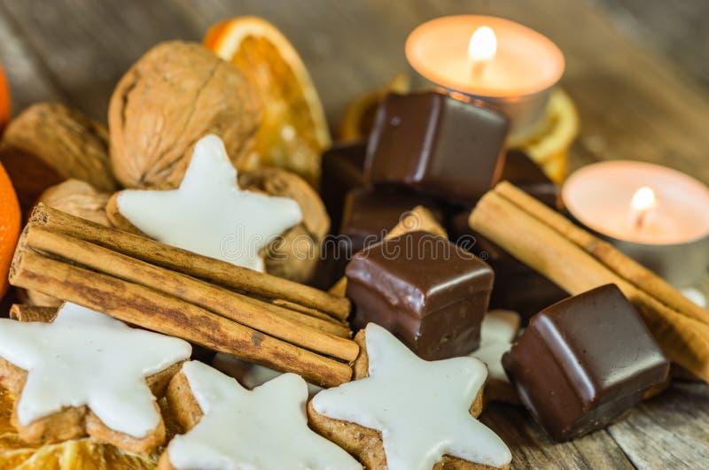 Weihnachtssternförmige Plätzchen, -schokolade, -nüsse, -zimt und -kerzen auf Holztisch stockfotografie