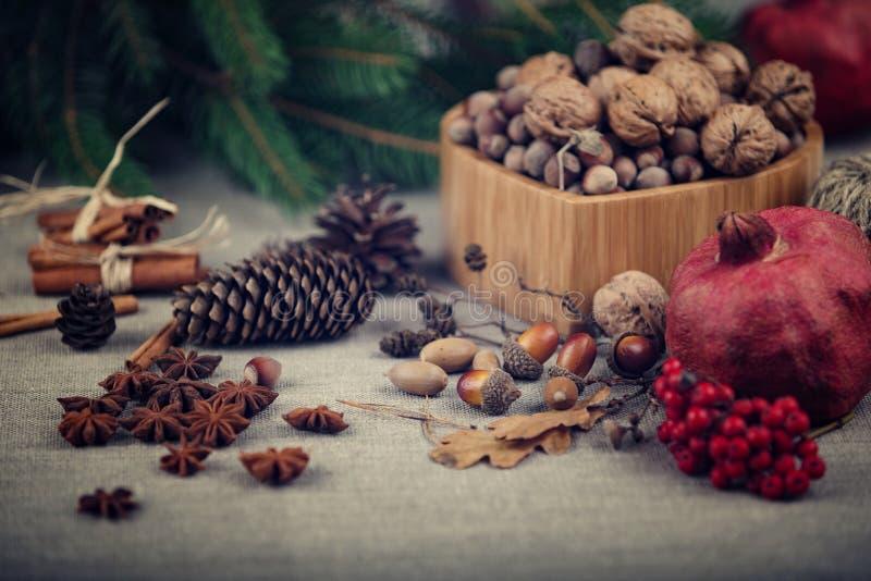 Weihnachtsstillleben von Nüssen, Fichtenzweige, Eicheln, Erlenkegel und Granatapfel, ausgebreitet auf rauem Gewebe stockfotografie