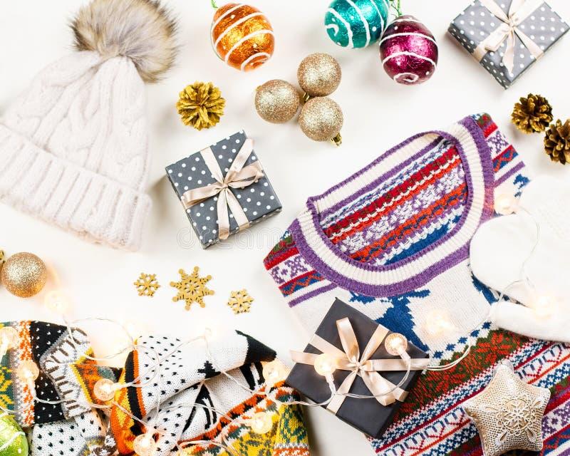 Weihnachtsstimmungszusammensetzung mit Weihnachtsstrickjacke, -hut, -geschenken und -lichtern Flache Lage des Winterkonzeptes, Dr stockfoto