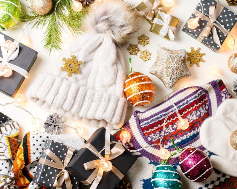 Weihnachtsstimmungszusammensetzung mit Weihnachtsstrickjacke, -hut, -geschenken und -lichtern Flache Lage des Winterkonzeptes, Dr stockbilder