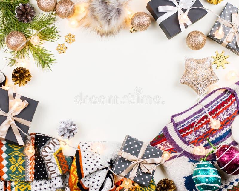 Weihnachtsstimmungszusammensetzung mit Weihnachtsstrickjacke, -hut, -geschenken und -lichtern Flache Lage des Winterkonzeptes, Dr lizenzfreie stockbilder