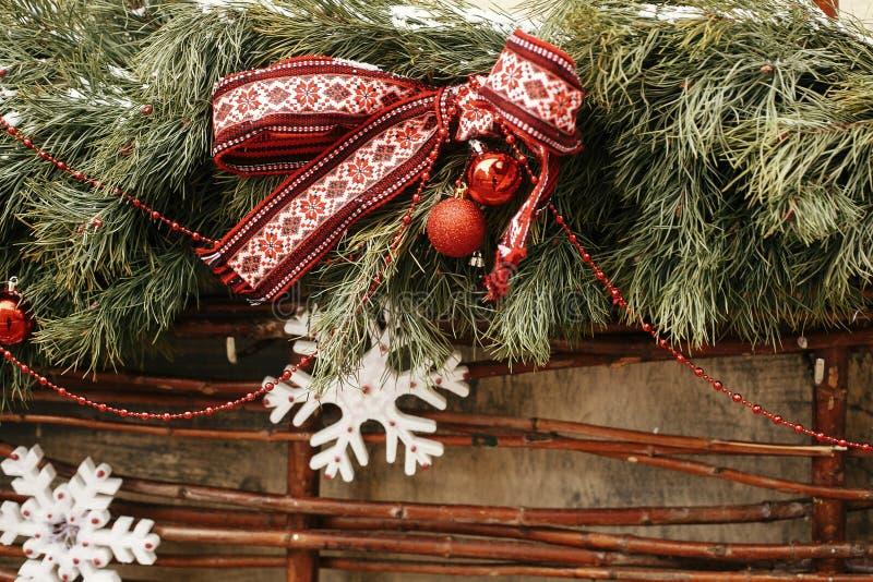 Weihnachtsstraßendekoration Stilschneeschneefickereien mit festlich rotem Bogen, Schneeflocke, Bälle auf Fensterladen im Urlaub stockbilder