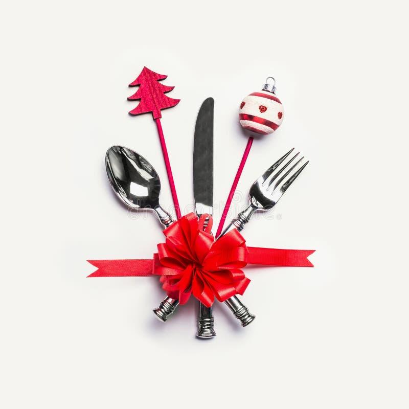 Weihnachtstabellengedeck mit Tischbesteck, rotem Band und minimaler Dekoration auf weißem Schreibtischhintergrund, Draufsicht Pla stockbilder