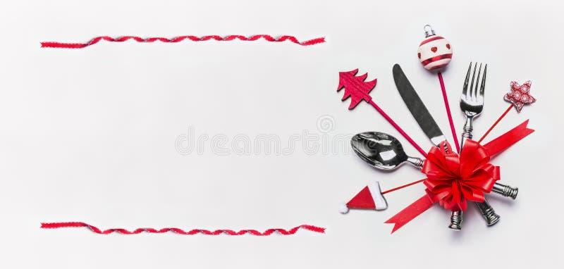 Weihnachtstabellengedeck mit Tischbesteck, rotem Bandrahmen und Dekoration mit Kopienraum auf weißem Schreibtischhintergrund, Dra lizenzfreie stockfotografie