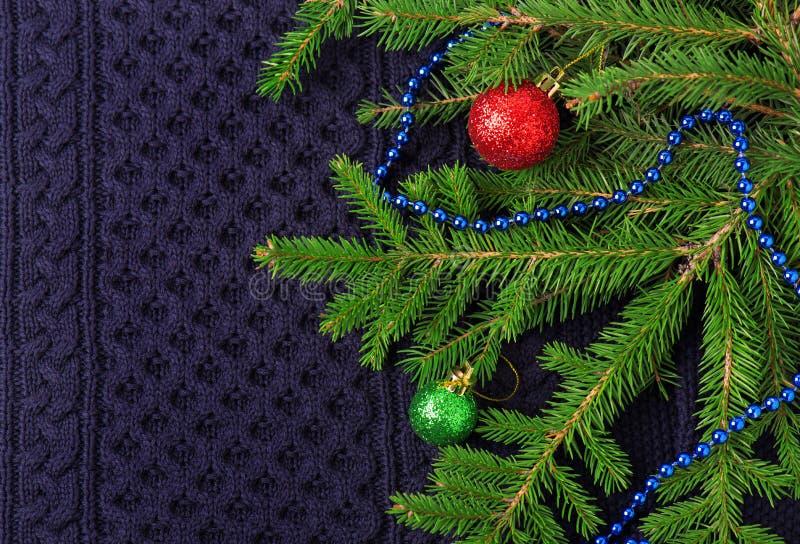 Weihnachtstannenbaum mit Dekoration auf dunkelblauem gestricktem Wollhintergrund stockbild