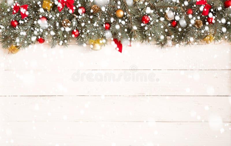 Weihnachtstannenbaum mit Weihnachtsdekorationen und -lichtern auf weißem hölzernem Hintergrund mit Schnee stockfotografie