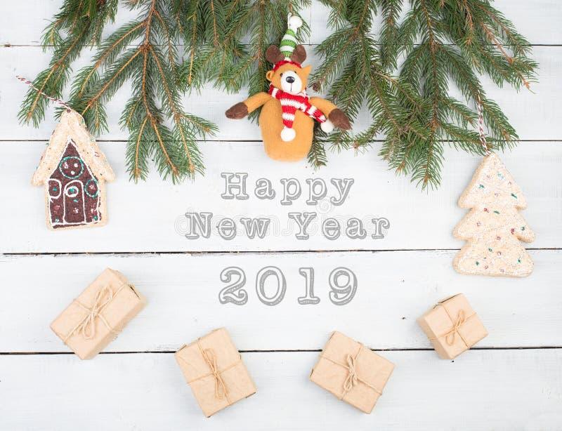Weihnachtstannenzweige, Geschenkboxen, Lebkuchenhaus, Weihnachtsbaum, Teddybär und Text lizenzfreie stockbilder