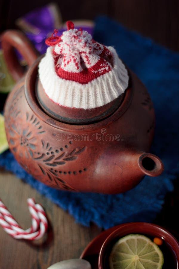 Weihnachtsteekanne mit dem roten Sankt-Hut auf ihm lizenzfreie stockfotos
