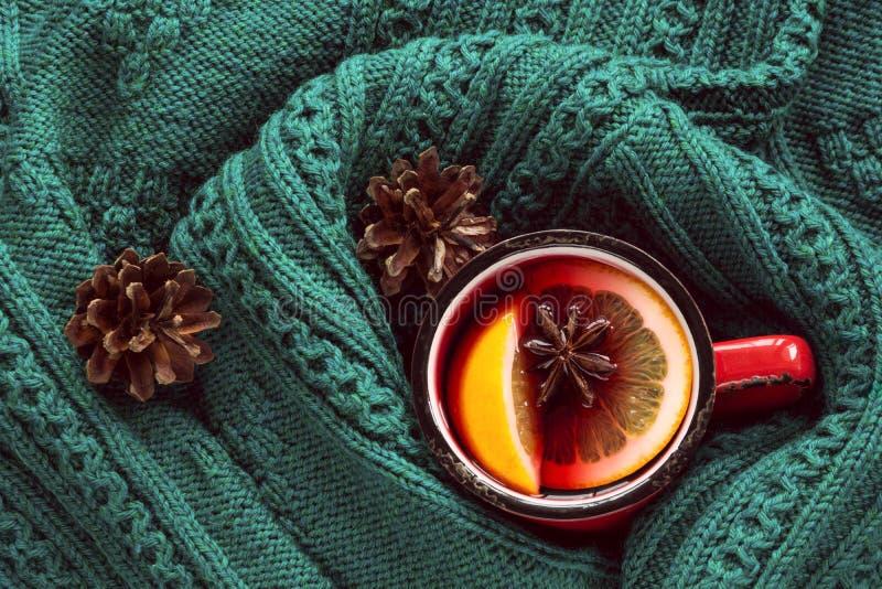 Weihnachtstraditioneller heißer Glühwein im roten Becher mit dem Gewürz eingewickelt in der warmen grünen Strickjacke stockfotografie