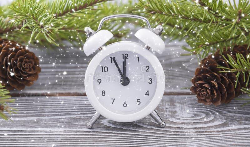 Weihnachtsuhr ist- ein weißer Wecker mit einer Winterordnung Holz und Kegel lizenzfreie stockfotografie