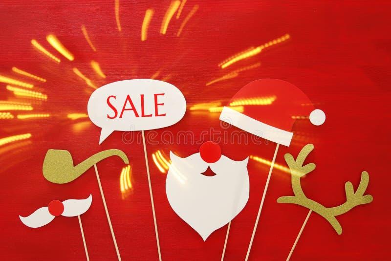 Weihnachtsurlaubseinkäufekonzept Weihnachtsmann-Rot und Barthut auf rotem hölzernem Hintergrund stockfotos