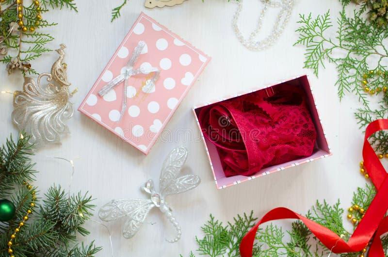Weihnachtsvergoldung für Frauen Rote Spitzewäsche auf dem dekorativen Ne lizenzfreie stockfotos