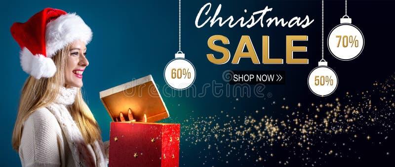 Weihnachtsverkaufsmitteilung mit der Frau, die eine Geschenkbox öffnet lizenzfreie stockfotografie
