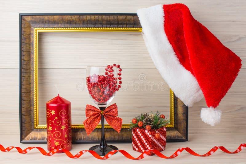 Weihnachtsverzierungen auf hölzernem Hintergrund Glas, Kerze, Geschenk, Hut Santa Claus stockbilder