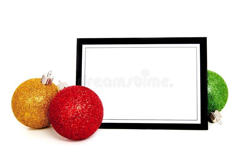 Weihnachtsverzierungen/Flitter um eine Anmerkungskarte stockfoto