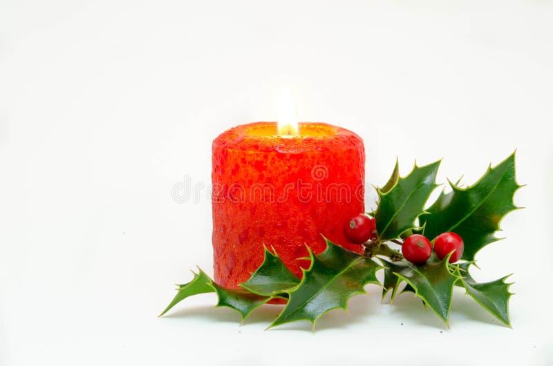 Weihnachtsverzierungen - rote Kerze und grüne Stechpalme lizenzfreie stockfotografie