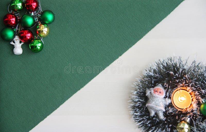Weihnachtsverzierungen, Schneemann, Santa Claus, neues Jahr ` s Lametta, brennende Kerze auf einem grünen Hintergrund stockbild