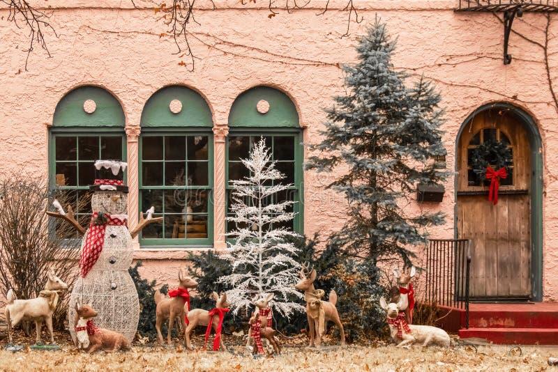 Weihnachtswaldverzeichnis mit Schneemann und Rotwild außerhalb der Fenster des rosa Stuckhauses sein--ribboned lizenzfreies stockbild