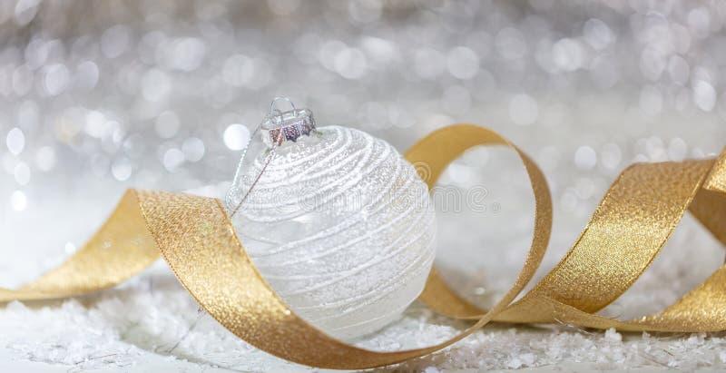 Weihnachtsweißer Ball, goldenes Band und Schnee, abstrakter bokeh Lichthintergrund stockbild