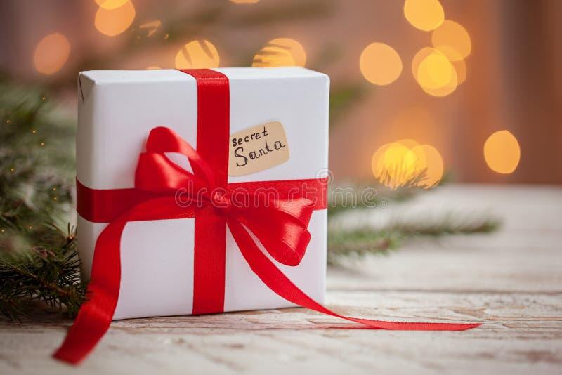 Weihnachtsweißer Kasten oder -geschenk mit rotem Band für geheime Sankt auf Holztisch lizenzfreies stockfoto