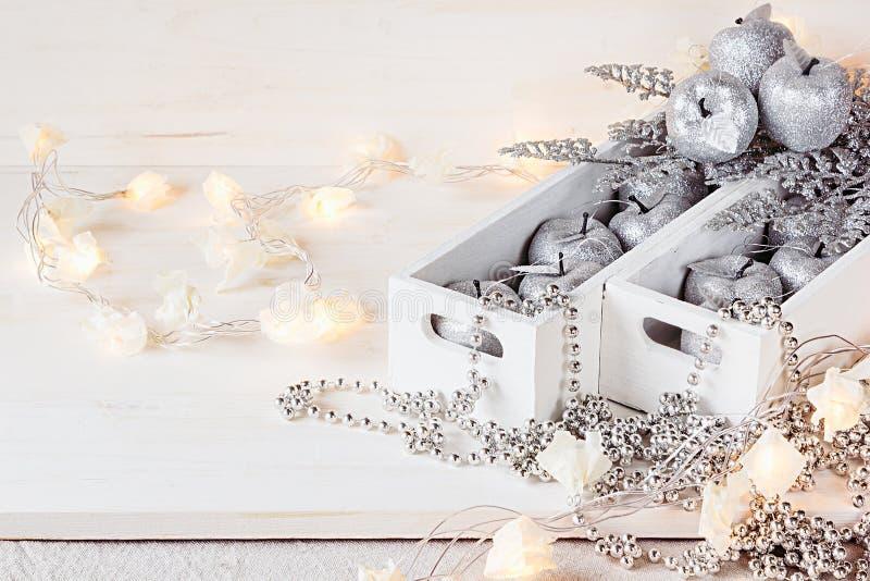 Weihnachtsweiche silberne Äpfel und -lichter, die in den Kästen auf einem hölzernen weißen Hintergrund brennen lizenzfreies stockbild