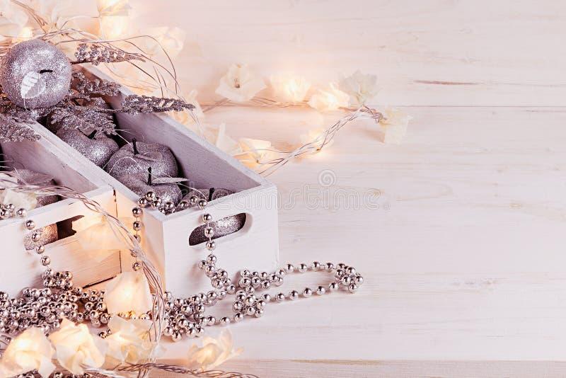 Weihnachtsweiche silberne Äpfel und -lichter, die in den Kästen auf einem hölzernen weißen Hintergrund brennen stockbilder