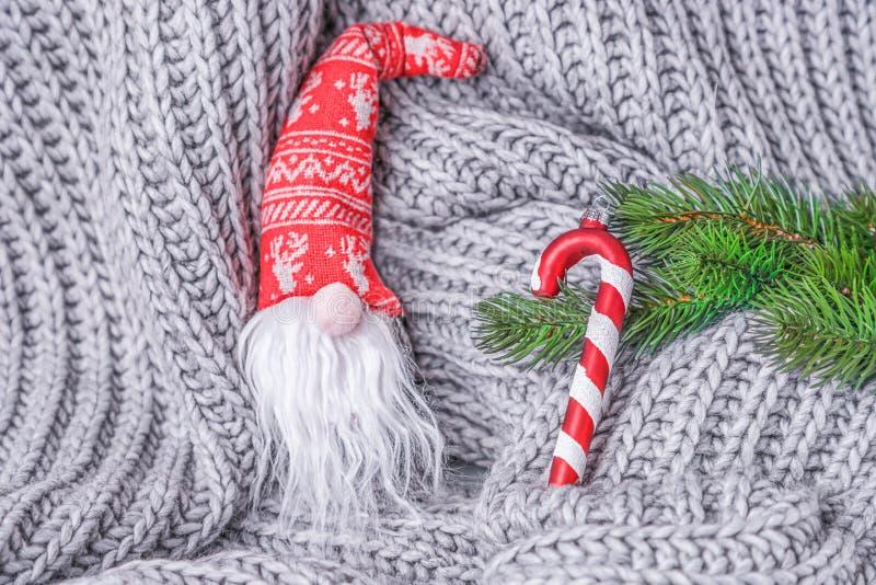 Weihnachtsweiche Spielzeugzwerge, Weihnachtsbaum und gestreifte Zuckerstange auf einem grauen gestrickten Hintergrund stockfotos