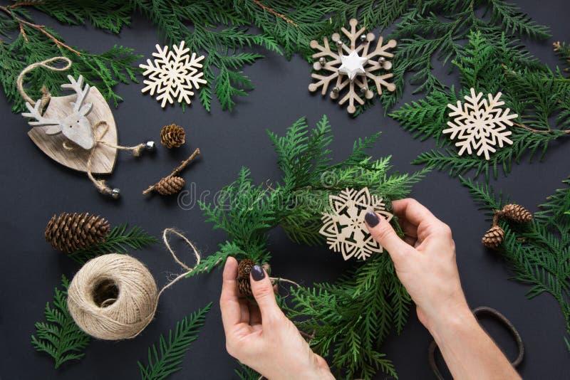 Weihnachtswerkstatt des Kranzes, des Dekors, der Schnur, der Zweige und der Schneeflocken Frau bereiten einen Kranz vor Oberseite lizenzfreie stockfotografie