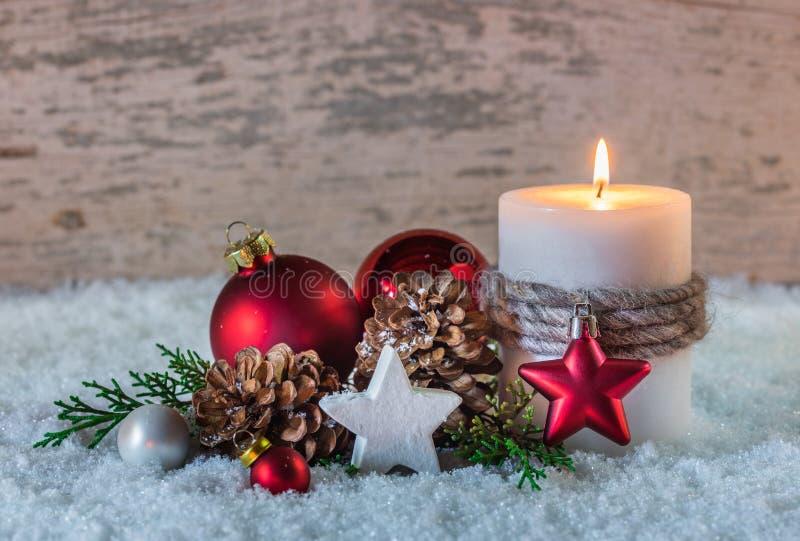 Weihnachtswinterdekoration mit brennender Kerze auf Schnee und hölzernem Hintergrund lizenzfreies stockfoto