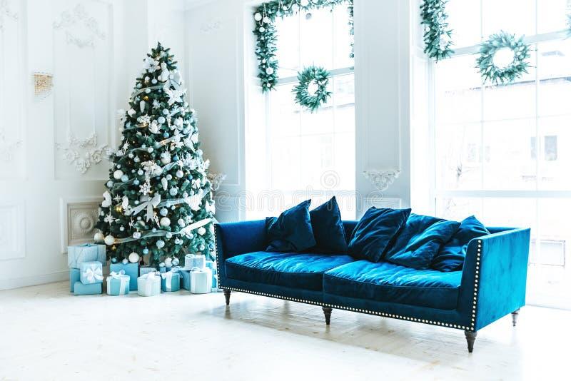 Weihnachtswohnzimmer mit einem Weihnachtsbaum, Sofa, Geschenken und einem großen Fenster Schönes neues Jahr verzierte klassischen stockfotos