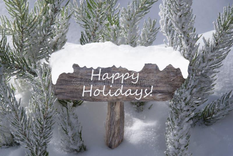 Weihnachtszeichen-Schnee-Tannen-Baumast-Text frohe Feiertage stockfoto