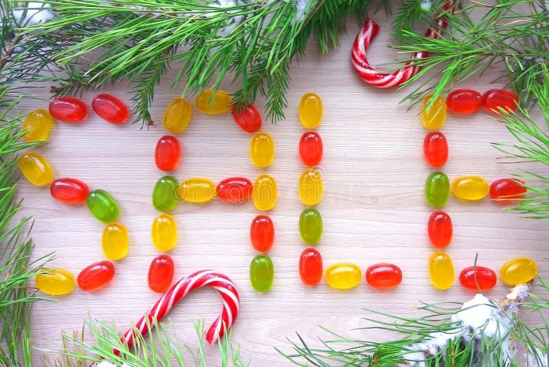Weihnachtszeichenverkauf gemacht von den Karamellsüßigkeiten mit schneebedeckten Tannenbaumasten auf hölzernem Hintergrund lizenzfreies stockfoto