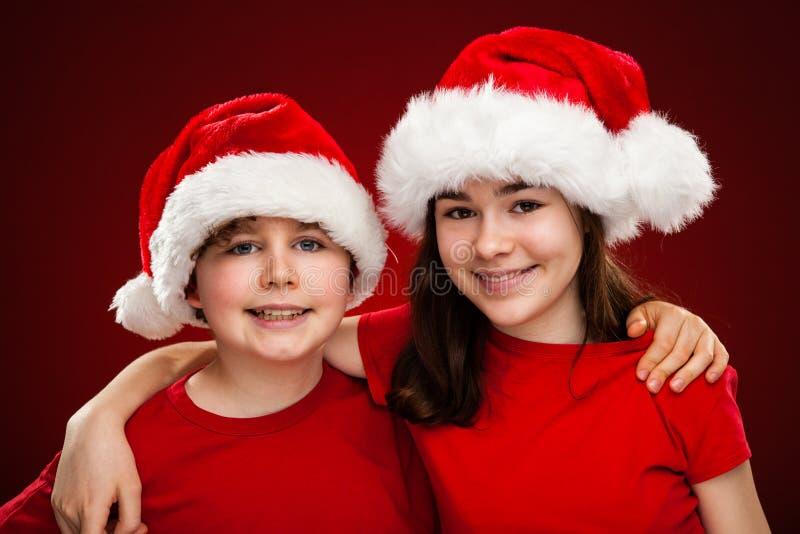 Weihnachtszeit- Mädchen und -junge mit Santa Claus Hats stockfoto