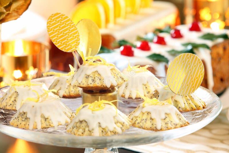Weihnachtszitronen-Mohnmuffins auf der verzierten Tabelle stockfotografie