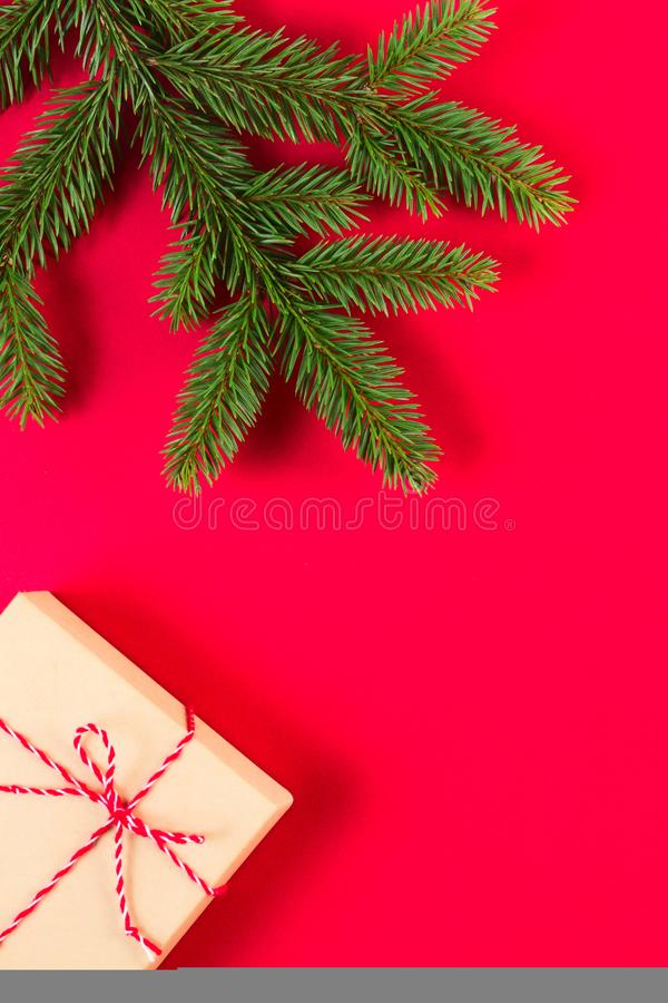 Weihnachtszusammensetzung auf rotem Hintergrund Grüner Tannenbaumast und -Präsentkarton lizenzfreie stockfotografie