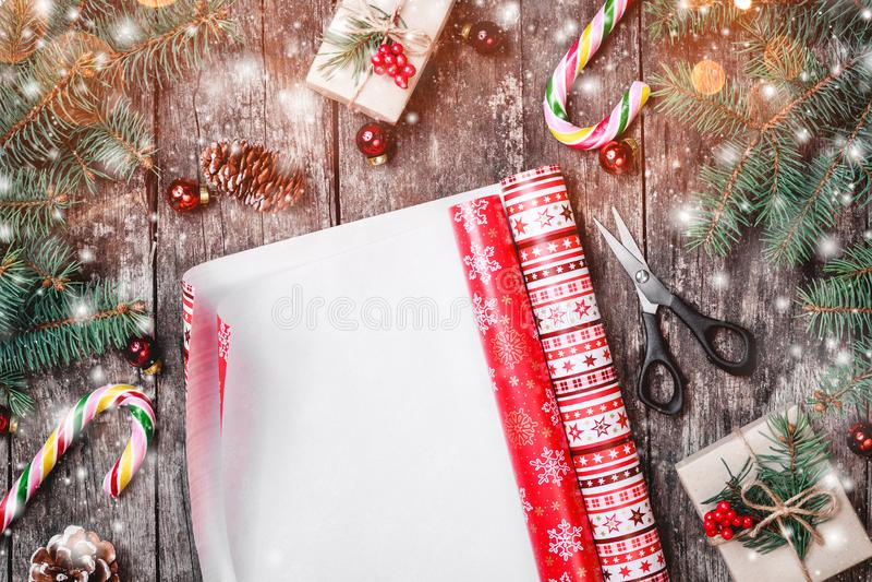 Weihnachtszusammensetzung mit einwickelndem Weihnachten, Tannenzweige, Geschenke, Kiefernkegel, rote Dekorationen auf hölzernem H lizenzfreies stockbild