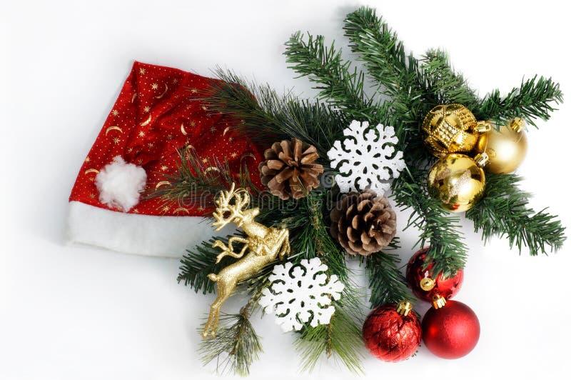 Weihnachtszusammensetzung mit Santa Claus-Hut, Tannenbaum, Kegeln, Bällen und Schneeflocken lizenzfreie stockfotos